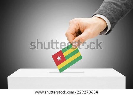 Voting concept - Male inserting flag into ballot box - Togo - stock photo