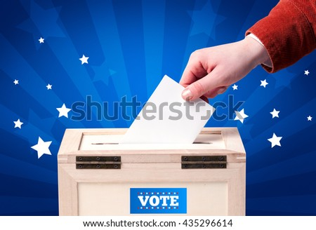Voting hand with ballot and wooden box - stock photo