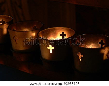 Votive candles burning in a darkened cathedral. - stock photo