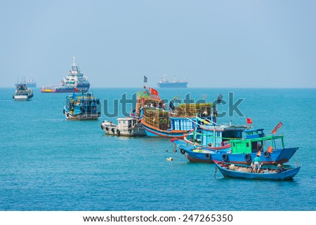 VUNGTAU, VIETNAM - JANUARY 15, 2015: Several ships and boats are at an anchor and move at the city port. The city is popular among Saigon people as sea resort. - stock photo