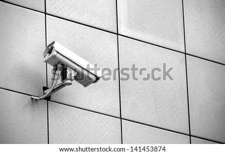 W/B CCTV camera on a wall watch rigth - stock photo