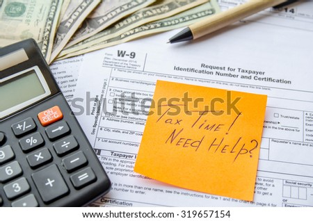 W-9 tax form as a business concept with pen, calculator and sticker