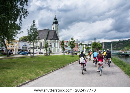 wachau Valley,Austria-May 9,2014:a group of cyclists through a village on the banks of the Danube on the famous Austrian bike path during a cloudy day - stock photo