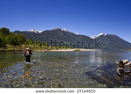 wading across the river - stock photo
