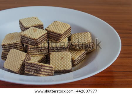 Wafer biscuits on saucer on a wooden table