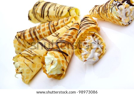 Wafer rolls with cream topped with nuts and chocolate