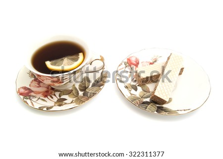 wafers and cup of tea with lemon on white closeup