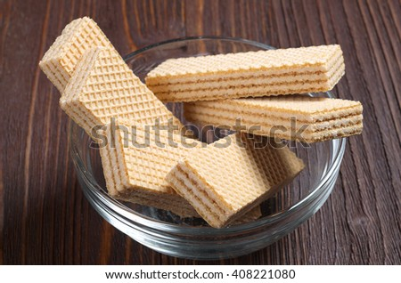 Wafers in glass bowl on wooden table - stock photo
