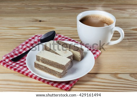 Wafers with chocolate and cup of hot coffee on rustic table