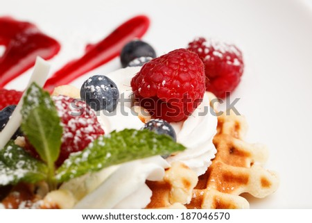 Waffle and cream topped with fresh blueberries and raspberries and garnished with peppermint, focus to a ripe raspberry