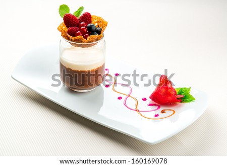 Waffle basket with fresh berries and cup of coffee and chocolate mousse with vanilla sauce  - stock photo