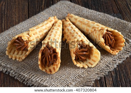 Waffle cones with sweet boiled condensed milk on rustic wooden table