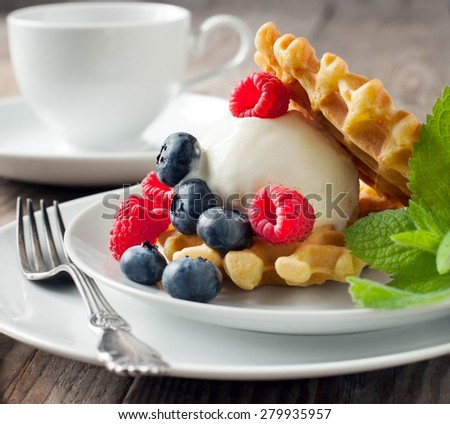 Waffle decorated with ice cream scoop and berries