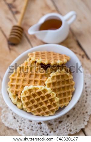 Waffle in a bowl on a wooden floor.