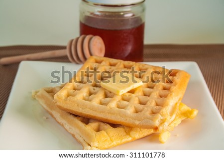waffle on a white plate with honey and butter