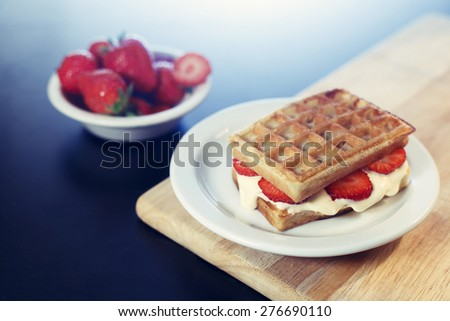 Waffle sandwich with caramel ice cream dessert on white plate with strawberries  - stock photo