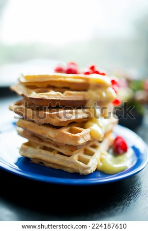 waffles for breakfast with strawberries, redcurrants and syrup - stock photo
