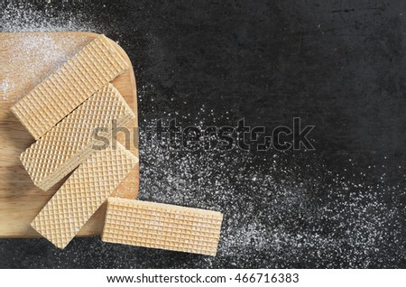 Waffles on kitchen board on a black metal background, top view