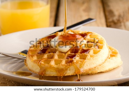 Waffles - This s a photo of a couple waffles being soaked in syrup. Shot on a wooden table with a shallow depth of field. - stock photo
