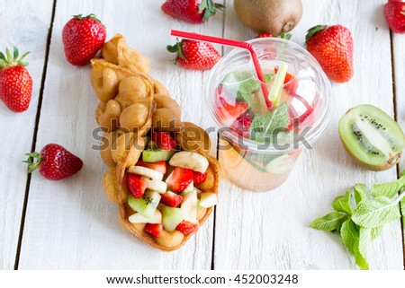 waffles with fruits, strawberries, apple and kiwi , and lemonade on the wooden table - stock photo