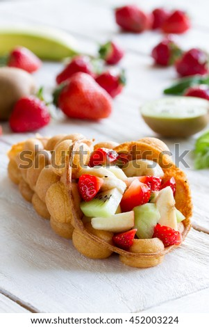 waffles with fruits, strawberries, apple and kiwi , on the wooden table - stock photo