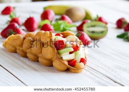waffles with fruits, strawberries, apple and kiwi on the wooden table - stock photo