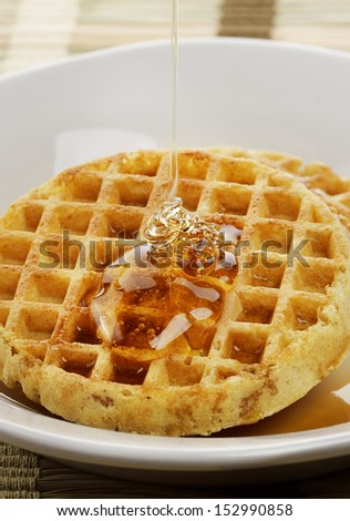Waffles With  Maple Syrup And Honey In A White Plate