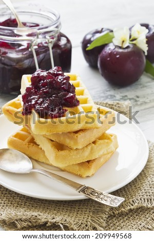 waffles with plum jam and ripe plums on the table.selective focus - stock photo