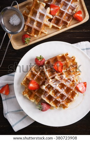 waffles with syrup and fresh strawberry in white plate