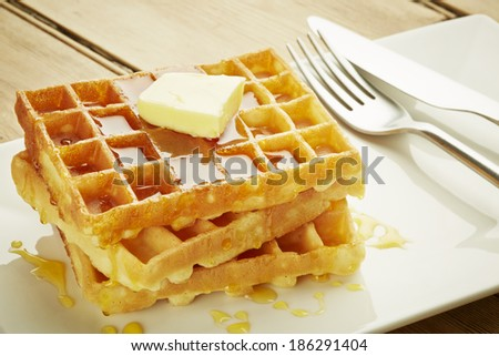 Waffles with syrup on white dish and wooden table top - stock photo