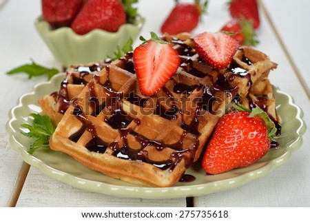 Waffles with topping and strawberries on a white background - stock photo