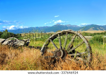 Wagon and wheels lay abandoned in deep grass along the highway in Paradise Valley, Montana.  The Absaroka Mountains loom in the distance.