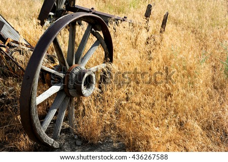 Wagon wheel axles lay rotting in a field.  Wheels have metal staves and wooden hubs and spokes.  Wagon lays in a field in Wyoming. - stock photo
