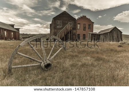 Wagon wheel with old building in the background - stock photo