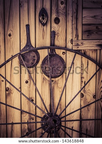 Wagon wheel with western themed objects and worn weathered wood. - stock photo