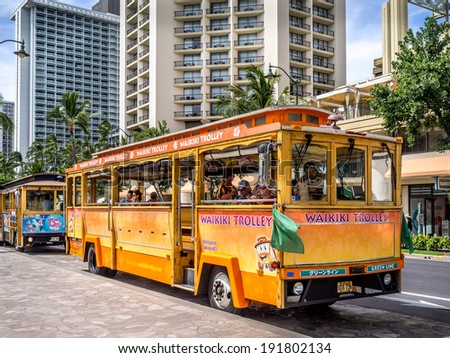 WAIKIKI, HAWAII - APRIL 29: Waikiki Trolley bus on Kalakaua avenue in Waikiki on April 29, 2014. The Waikiki Trolley bus is a popular shuttle bus that takes tourists around scenic Waikiki in Honolulu. - stock photo