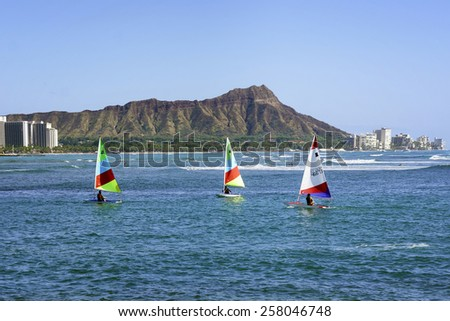 WAIKIKI, HAWAII - FEBRUARY 18, 2015: View of boats floating past Diamond Head in Honolulu, Hawaii.  Diamond Head is a defining feature of the view known to residents and tourists of Waikiki. - stock photo