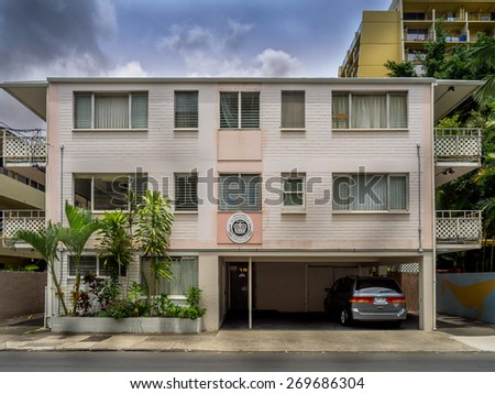 WAIKIKI, HI - APRIL 26: Older apartment building on April 26, 2014 in Waikiki, Hawaii. Waikiki has many apartments buildings that have seen better days, but support the surf culture.  - stock photo