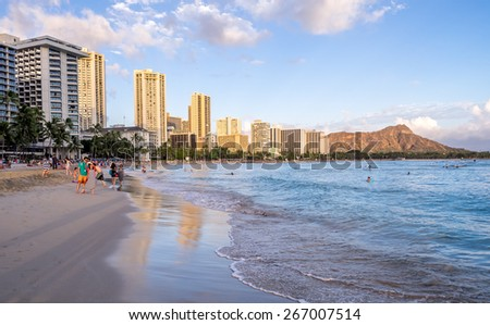 WAIKIKI, HI - APRIL 27 - Tourists sunbathing and surfing at sunset on Waikiki beach April 27, 2014 in Oahu. Waikiki beach is beachfront neighborhood of Honolulu, best known for white sand and surfing. - stock photo