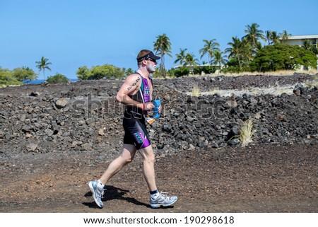WAIKOLOA, HI USA - APRIL 3, 2011: Unidentified runner on the Lavaman Triathlon in Waikoloa, Hawaii. It is held in Olympics format: 1.5 km swimming, 40 km biking and 10 km running. - stock photo