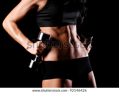 waist and hands of a beautiful sporty muscular woman working out with two dumbbells, isolated against black background (focus on the belly)