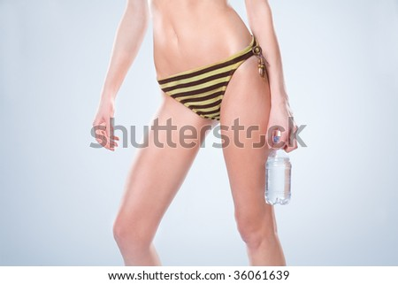 Waist-down view of woman standing in a swimsuit and holding a water bottle