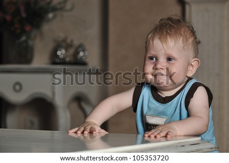 Waist portrait of a baby boy in a blue shirt leaning against a coffee table smiling - stock photo