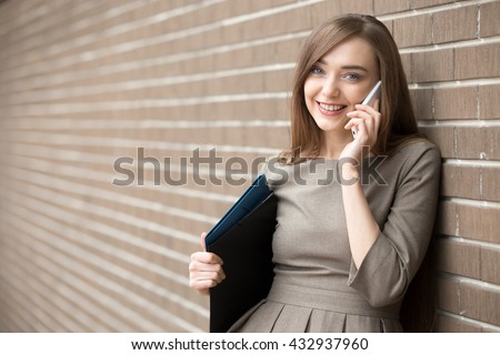 Waist portrait of cheerful young woman standing in the street beside brick wall, talking on smartphone. Happy beautiful caucasian woman using mobile phone, making call, looking at screen. Copy space - stock photo