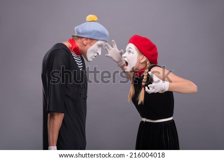 Waist-up horizontal portrait of couple of two mimes standing face to face and screaming on each other, male mime very angry isolated on grey background with copy place - stock photo