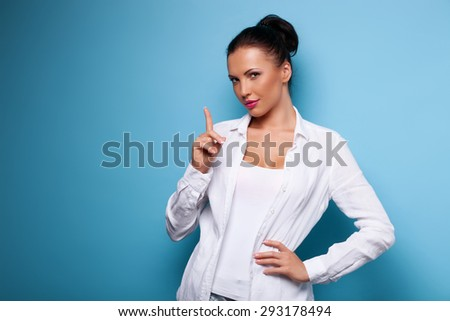 Waist up of beautiful woman raising her finger up warningly. She advices following her tips. She is looking seriously at the camera. Isolated on blue background and there is copy space in left side - stock photo