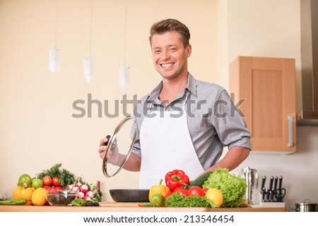 waist up of man holding frying pan lid. guy preparing healthy food at kitchen - stock photo