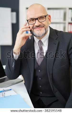 Waist Up of Mature Professional Businessman Wearing Suit and Eyeglasses Looking Confident and Smiling to the Side While Talking on Cell Phone at Desk in Modern Office Workplace - stock photo
