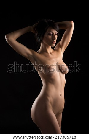 waist up of nude young woman in front of black background. naked body and breast of young girl looking down - stock photo