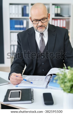 Waist Up of Serious Mature Professional Businessman Wearing Suit and Eyeglasses Looking Down and Studying Paperwork in Binder While Sitting at Desk in Modern Office Workplace - stock photo